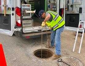 Lowering ROVVER X into Manhole